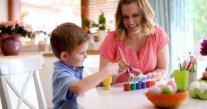 Modern och sonen målar ägg arkivbilder