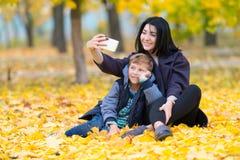 Modern och sonen som poserar för en selfie i, parkerar fotografering för bildbyråer