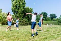 Modern och sonen som spelar badminton parkerar in, i sommar Arkivfoto