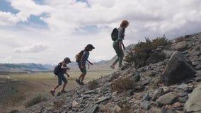 modern och två barn gick att fotvandra i bergen en grupp av handelsresande up berget familjhandelsresande i lager videofilmer