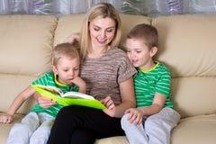 Modern och två söner läser en bok arkivfoto