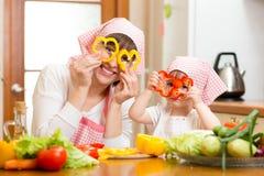 Modern och ungen har gyckel som förbereder sund mat Royaltyfri Bild