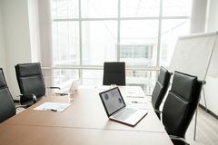Modern office boardroom interior with conference table and big w. Modern office boardroom interior with laptops documents on conference table and big window Royalty Free Stock Photo