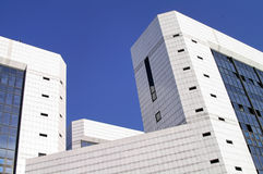 Modern office building (2). Modern sleek office building with white marble tiles in a blue sky Royalty Free Stock Images