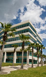 Modern Office Building. In office park with trees and partly cloudy afternoon sky Royalty Free Stock Photo