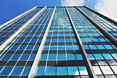 Modern office building. Low angle view of blue sky and cloudscape reflecting on windows of high rise modern office building stock image