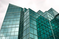 Modern Office Building. This is a modern glass office building reflecting dark clouds Stock Photography
