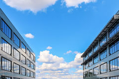Modern office building against blue cloudy sky Royalty Free Stock Images