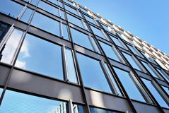 Modern office building. Architectural details of modern  building. Panoramic and perspective wide angle view to steel blue background of glass building Royalty Free Stock Photos