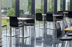 Modern office building cafeteria seating area. Cafeteria seating area with tables and chairs in a modern office building with glass windows. Outside overlooking stock photo