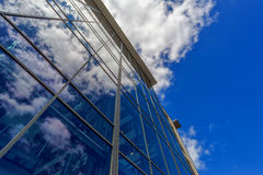 Modern Office Building with Clouds Reflecting on Glass Facade Royalty Free Stock Photos