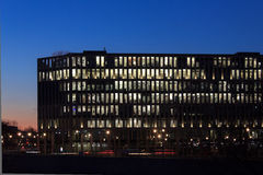 Modern office building facade, people working at night Stock Image