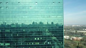Modern office building facade reflecting cityscape on a sunny day stock video footage