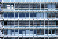 Modern office building. The modern facade of an office building with window rows and metal blinds Stock Image