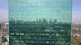 Modern office building glass facade reflecting cityscape stock footage