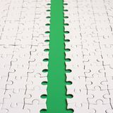 The green path is laid on the platform of a white folded jigsaw puzzle. Texture image with copy space for text stock photos
