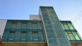 Modern office building with glass transparent walls against the blue sky Stock Photos