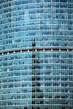 Modern office building glass wall front view close-up. Modern office building glass wall with many large panoramic windows in business cluster vertical front Stock Photography