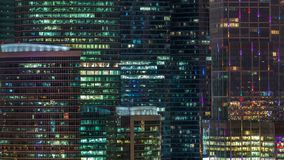 Modern office building with glowing windows at night timelapse. Moscow city. Close up view from rooftop. Pan up stock footage