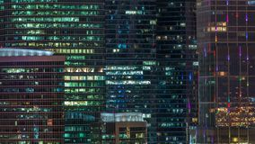 Modern office building with glowing windows at night timelapse. Moscow city. Close up view from rooftop. Zoom in stock video