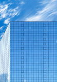 Modern office building made of blue glass and cloudy sky Royalty Free Stock Images