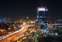 Modern office building next to the road overpass on the background of the industrial area by night Stock Photography