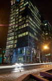 A modern office building and a night traffic Royalty Free Stock Images