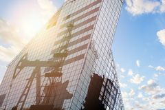 Modern office building with oil derrick on a background of the blue sky.  stock photo