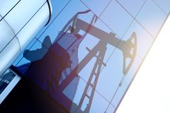 Modern office building with sign oil derrick on a background of the blue sky. Energy Concept.  royalty free stock photos