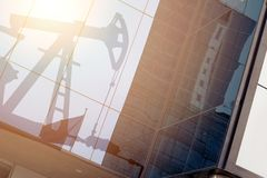 Modern office building with sign oil derrick on a background with sunlight. Energy Concept.  stock image