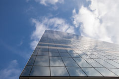 Modern office building on sky background with clouds reflection Royalty Free Stock Image