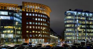 Modern office building and street with cars at night Stock Photo
