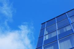 Modern office building with tinted windows against sky. Modern office building with tinted windows against blue sky stock image