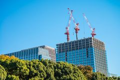 Modern office building under crane construction against blue sky Stock Photo