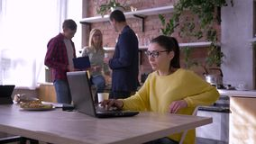 Modern office, business female wearing glasses works on laptop while collaborators eat sandwiches and communicate during stock video footage