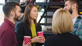 In a modern office center group of multiethnic workers while have a coffee break have a friendly conversation smiling