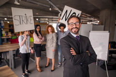 Modern office concept, director standing with his back to striking cowokers. Stock Photo