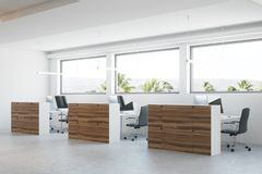 Wooden and white office interior. Modern office corner with a concrete floor, wooden columns and cubicles with computer tables. 3d rendering mock up Royalty Free Stock Image