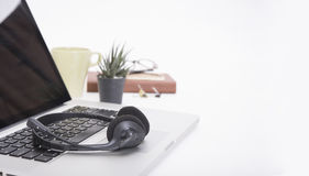Modern Office desk with computer, notebook, headset, paper book. Stock Photos