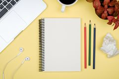 Modern office desk table with laptop and blank notebook page Royalty Free Stock Images