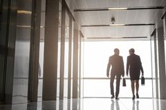 Full length rear view of mature colleagues talking while walking in office corridor stock photo