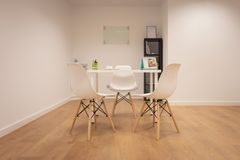 Modern office. Furniture set with table and chairs. Interior of minimalist office with white walls, wooden floor, wooden and white. Computer table and black royalty free stock image