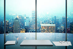 Modern office with glassy table, laptop and night megapolis city Stock Photo