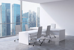 Modern office interior with huge windows and Singapore panoramic view. White leather on the chairs and a white table. A concept of Stock Image