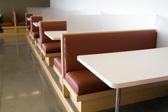 Modern office lunchroom clean view. Modern table and booth setup in an office lunchroom. Wide angle side view shows a long series of tables available. Very Royalty Free Stock Images