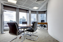 Modern office meeting room interior. Small modern office boardroom and meeting room interior with desks, chairs and cityscape view