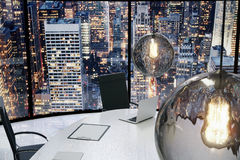 Modern office with vintage lightbulbs and city view at evening Royalty Free Stock Photography