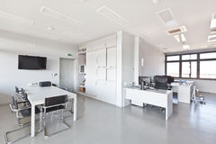 Modern office with white furniture. Cupboard, conference desk and walls and with plasma TV on the wall stock images