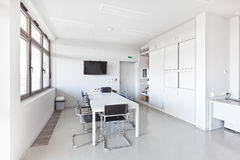 Modern office with white furniture. Cupboard, conference desk and walls and with plasma TV on the wall stock photography