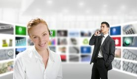 Modern office, woman and businessman, tv screen. Modern office with woman and businessman over tv screen wall Royalty Free Stock Images